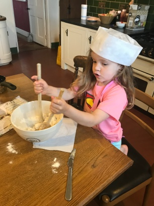 girl in chefs hat stirring cake mixture