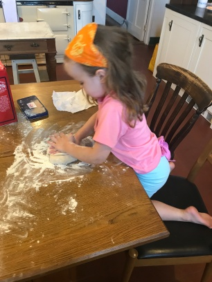 girl kneading dough on kitchen table