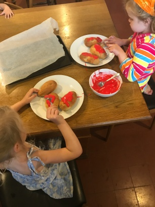 two girls icing sticky buns with red icing