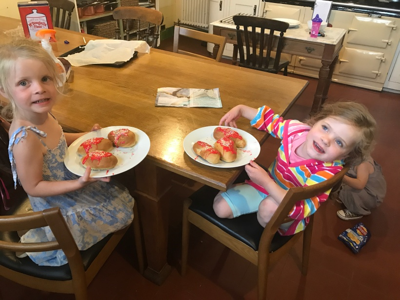 two children happy with cakes they have made