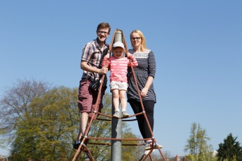 family standing at the top of rope pyramid