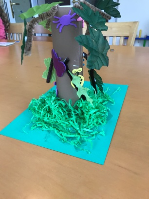 use shredded paper to make grass and decorate your tree with animal stickers