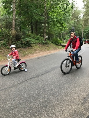 girl riding bike with daddy at center parcs