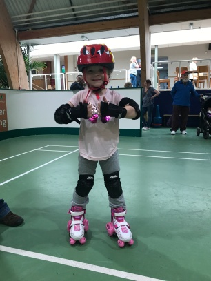 child roller skating wearing helmet and knee pads