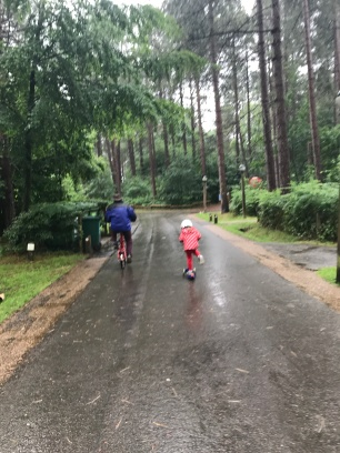 child cycling next to grandad in the forest