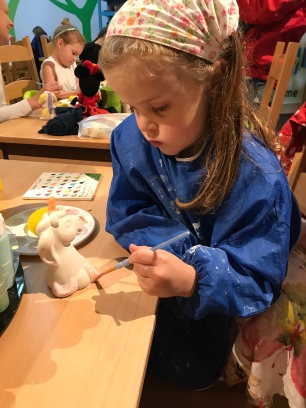 child doing pottery painting
