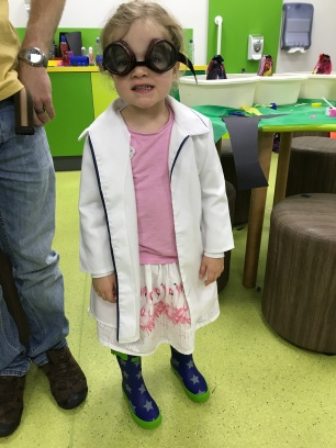 child dressed as mini scientist in lab coat and goggles